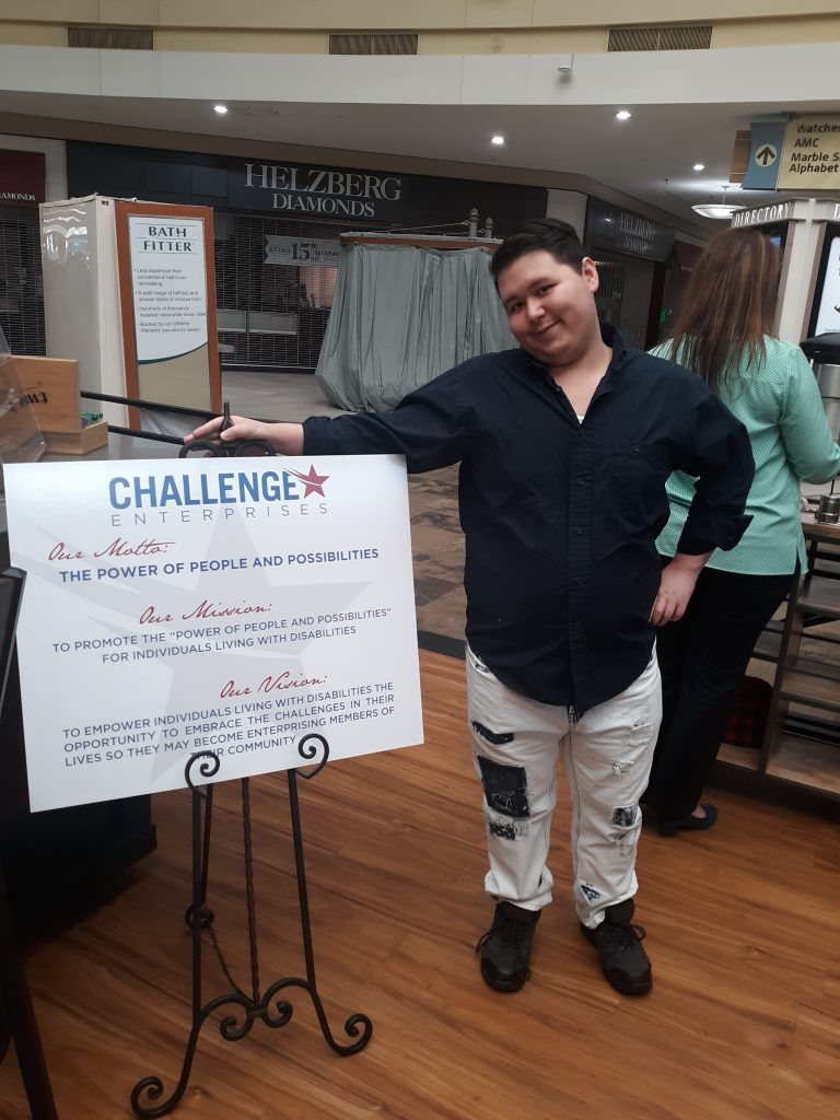 Person Standing next to Challenge Enterprises mission poster