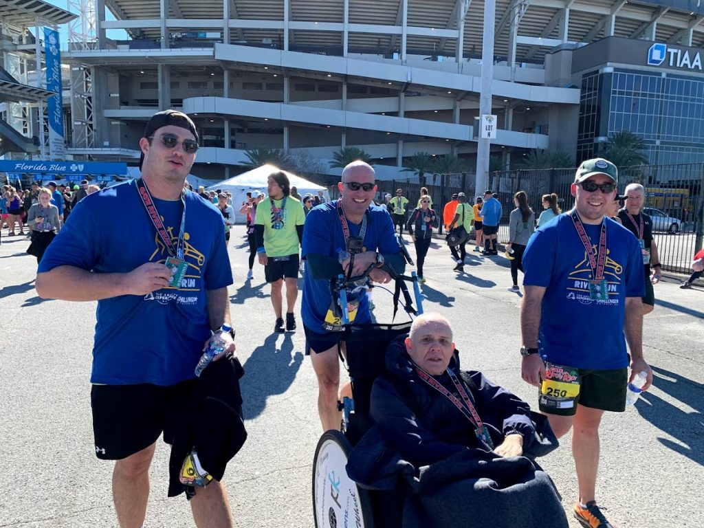 3 Runners talking a picture with a person with different abilities in a wheel chair